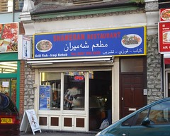 "A small ground-floor terraced shopfront with a sign reading ""Shameran Restaurant"" and ""Grill Fish - Iraqi Kebab"".  A sign on the window reads ""Halal"".  A projecting sign shows a shisha pipe, and the surround of the shopfront is a faux grey stone wall."