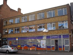 "The same three-storey building as in the first image above, but this time with Sure Start branding on the ground floor windows and a poster advertising the ""Croydon Play Zone""."