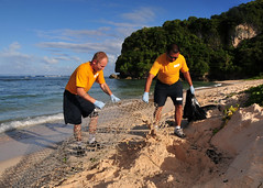 TUMON, Guam (Dec. 9, 2011) Hull Maintenance Technician 1st Class Steven Mullin and  Hull Maintenance Technician 2nd Class Zeus Millena, both assigned to the submarine tender USS Frank Cable (AS 40), remove trash from the beach during a community service project. (U.S. Navy photo by Mass Communication Specialist 1st Class Melvin Nobeza)