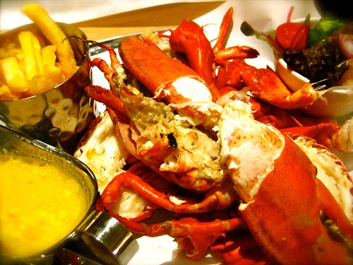Grilled lobster with salad and chips and garlic butter