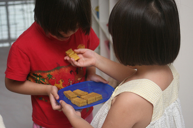 Jolie giving a piece of kueh lapis to Nadine