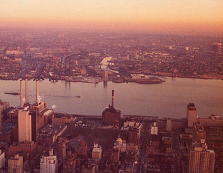 Smoggy sunset from the Empire State Building to the East River and Newtown Creek in Queens which was still industrial. The Con Edison plant gently emits a puff of light blue oil smoke from its smokestacks. New York. Sun Jan 21, 1973