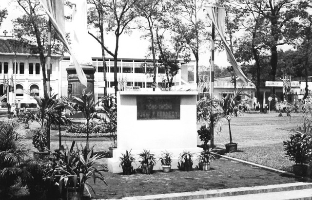 A plaque with John F. Kennedy's name on it flanked by two South Vietnamese flags in front of a large building