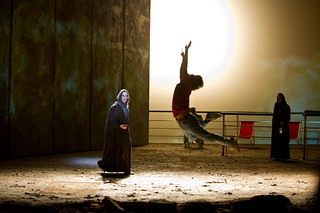 An actor leaps through the air on stage as two others in robes watch