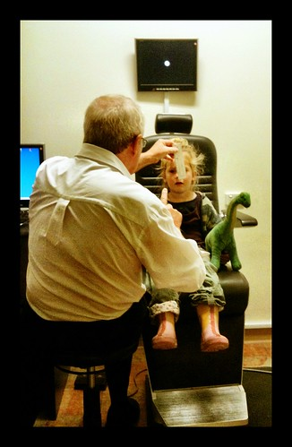 Small Z has her eyes tested. With dinosaur.