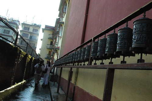 Westerners praying the prayer wheels, walking around Tharlam Monastery of Tibetan Buddhism, wet alley, wall, apartments, Sakya Lamdre, Bodha, Kathmandu, Nepal by Wonderlane