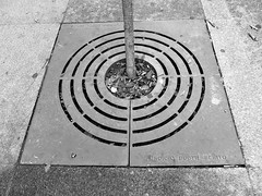 floor(0.0), outdoor structure(0.0), sidewalk(0.0), labyrinth(0.0), lane(0.0), manhole(0.0), manhole cover(0.0), road surface(0.0), flooring(0.0), pedestrian crossing(0.0), asphalt(1.0), symmetry(1.0), line(1.0), monochrome photography(1.0), circle(1.0), monochrome(1.0), black-and-white(1.0), infrastructure(1.0),