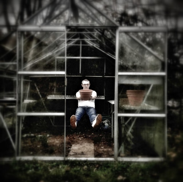 image of author floating in a greenhouse, offering a pot to the gods of gardening