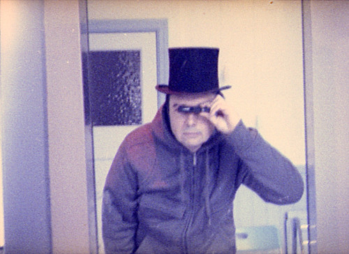 reflected self-portrait with Minox EC camera and undersized top hat. by pho-Tony