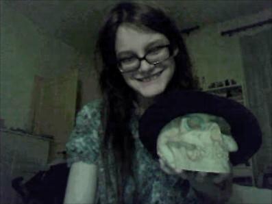 Photo d'une personne tenant un crâne qui porte un bérêt et a un rond de capsule de bouteille dans l'orbite. Le crâne a l'air de sourire de façon démoniaque, alors la personne fait de même.