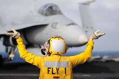 In this file photo, Aviation Boatswain's Mate (Handling) 3rd Class Alexis Lebrake, assigned to Air Department's V-1 Division, guides an F/A-18C Hornet as it taxis on the flight deck aboard aircraft carrier USS Carl Vinson (CVN 70) Dec. 31, 2011. (U.S. Navy photo by Mass Communication Specialist 2nd Class Benjamin Stevens)