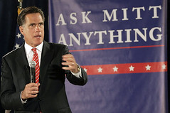 Mitt Romney in front of a sign that says ASK MITT ANYTHING. He is in a black suit with a red tie