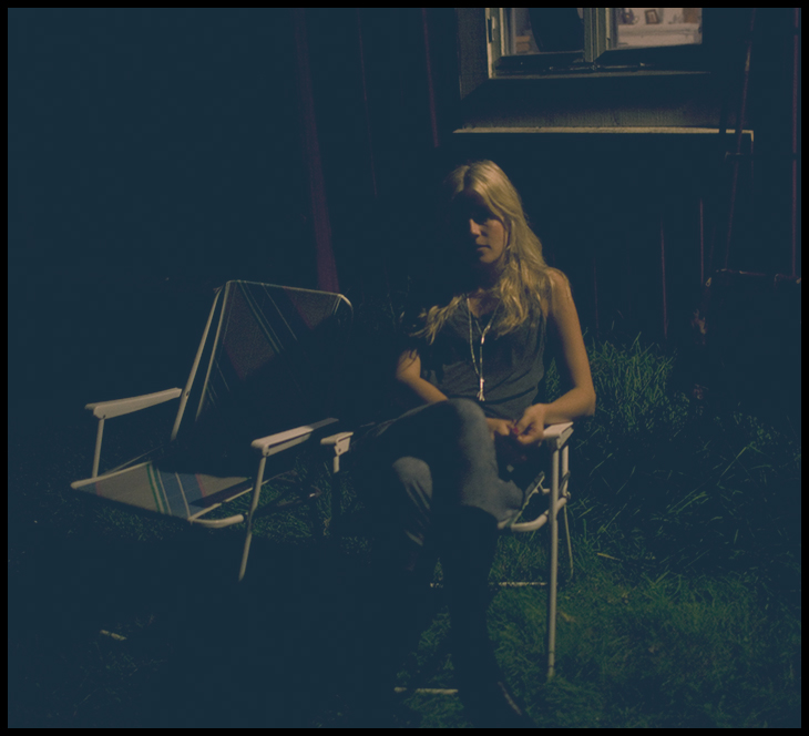 blonde girl in a chair (outside at night)
