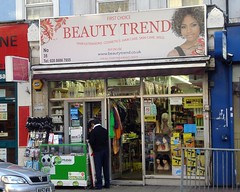 "A terraced shopfront with full-length windows and a glass door in the middle.  A small display stand against the left-hand window offers mobile phone accessories.  The sign above the frontage reads ""First Choice / Beauty Trend / Hair extensions. Cosmetics. Hair care. Skin care. Wigs. / Buy On Line / www.beautytrend.co.uk / For all your hair & beauty needs"". On the right-hand side of the sign is a head-and-shoulders photo of a light-skinned Black woman with blonde highlights in her curly brown hair, wearing a sleeveless black top."""
