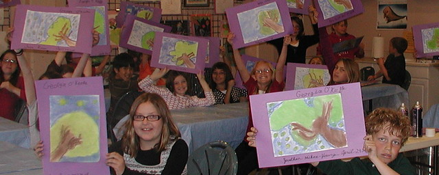 kids in art class holding up their art