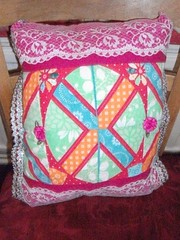 quilt(0.0), furniture(0.0), bed sheet(0.0), art(1.0), pattern(1.0), textile(1.0), patchwork(1.0), throw pillow(1.0), design(1.0), pink(1.0), cushion(1.0),