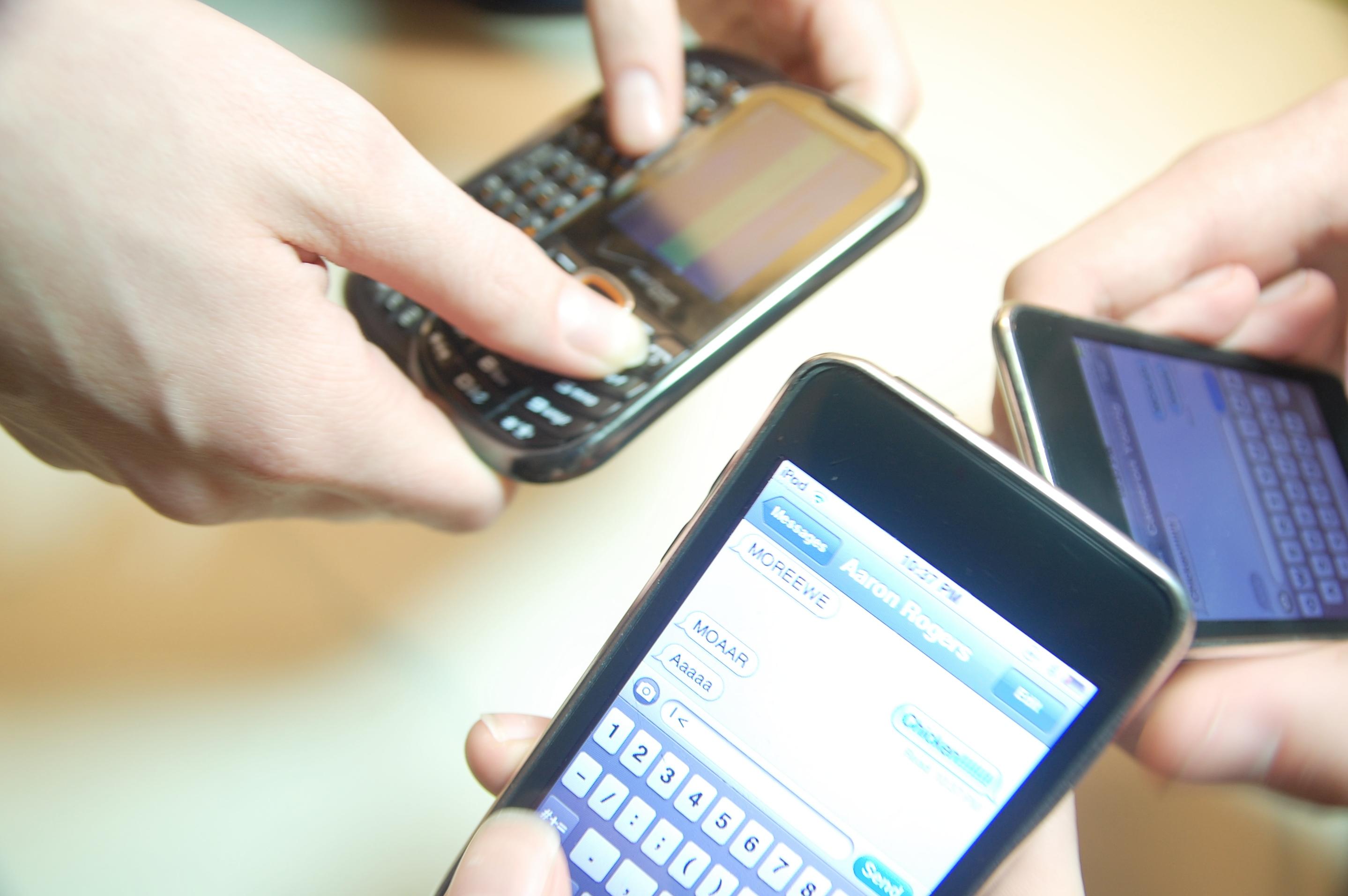 Three people texting using smartphones