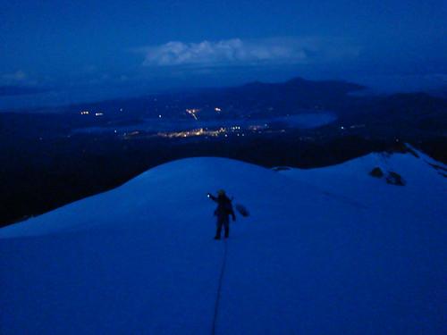 Ascenso nocturno con las luces del pueblo Cayambe al fondo