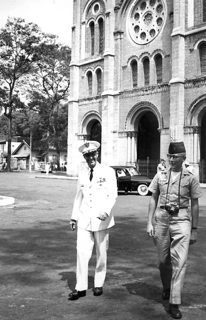 Two American military officers walking away from a cathedral in Saigon.