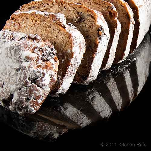Stollen slices and loaf reflected on black acrylic