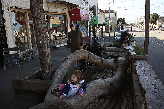 Willa Lolif, 2 1/2, plays on the eucalyptus trunk that provides seating in the parklet at Trouble Coffee on Judah Street.
