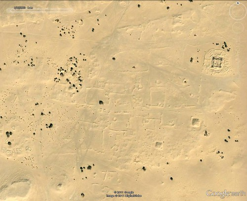 Satellite image of area of desert with archaeological interpretation of features: fortifications are outlined in black, areas of dwellings are in red and oasis gardens are in green. Castles in the desert – Satellites reveal lost cities of Libya (ERC Advanced Grant 2010) Copyright 2011 Google, image copyright 2011 DigitalGlobe