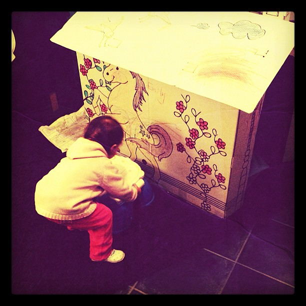 Emily draws on her paper gift house.