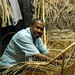 A craftsman make a chair from wicker
