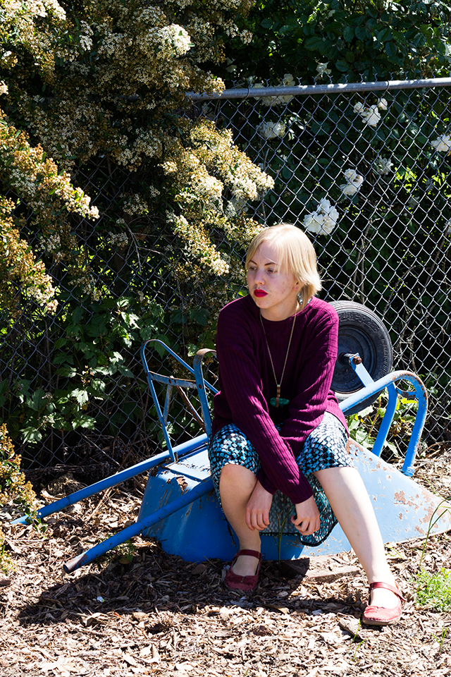 plum purple sweater, perched on an overturned blue wheelbarrow