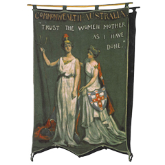 An Australian banner featuring two white women in robes that says TRUST THE WOMEN AS I HAVE DONE