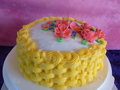 Here is a sample of a basket weave cake topped with royal icing flowers.  We love bright colors around Ooey Gooey.  Visit <a href='http://www.familysweetery.com' rel='nofollow'>www.familysweetery.com</a> for ordering information.