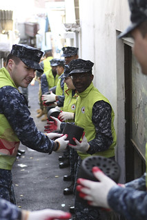 MASAN, Republic of Korea (Dec. 5, 2011) Sailors pass charcoal briquettes during a community service project assisting low income families. (U.S. Navy photo by Chief Information Systems Technician David Kelly)