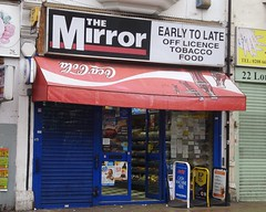 "A small terraced shopfront with a sign above reading ""The Mirror / Early To Late / Off Licence / Tobacco / Food"". A red canopy below this carries an upside-down Coca-Cola logo. A blue shutter is drawn down over the left-hand window of the shop, and small adverts are visible in the right-hand window. Three A-boards stand on the pavement, advertising a cash machine, a PP pay point, and a parcel service. The door of the shop is open, and shelves of packaged snacks are visible inside."