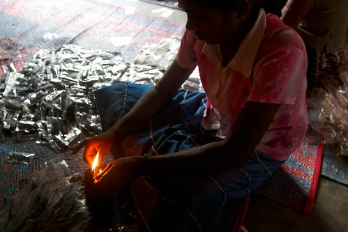 A woman sealing a spice packet with a kerosene flame in Malayalapuram