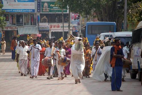 Eine Prozession mit Kalash Gefässen zieht zum Tempel, vorne gehen Musiker und als Esel ode Stier verkleidete Tänzer.