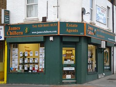 "A ground-floor corner shopfront painted in dark green with lettering in dark orange reading ""James Chiltern"" ""Estate Agents"".  A web URL is given in white.  The windows are covered in posters advertising properties."