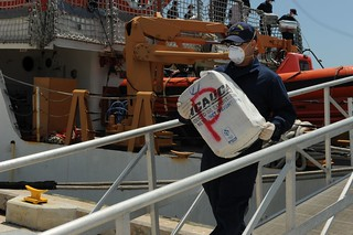 A crewmember aboard the Coast Guard Cutter Legare offloads a bale of cocaine at Coast Guard Base Miami Beach, Fla., April 15, 2014. The crew of the Legare offloaded a total of $110 million of cocaine that was seized in the Caribbean Sea. (U.S. Coast Guard photo by Petty Officer 3rd Class Mark Barney)