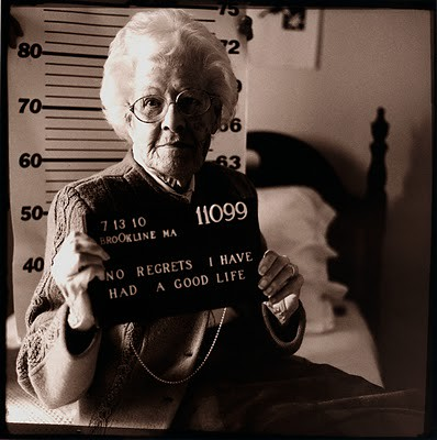 Black and white mugshot-style photo of an older white woman. Placard reads No regrets I have had a good life