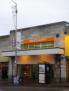 """The same railway station entrance but the sign now reads """"West Croydon"""" and is in white text on an orange background. The protruding sign now shows the London Overground roundel as well as the National Rail symbol, and the """"on"""" text has gone."""
