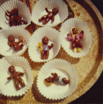 an array of paper muffin tin liners, each with a small brown baby doll inside