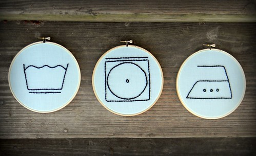 tre simboli della lavatrice ricamati su un quadretto e appesi