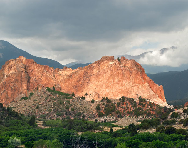 An iconic red stone mountain rises up against a stormy sky in Colorado's Garden of the Gods.