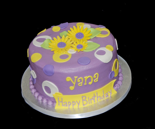 purple and yellow sassy circles birthday cake topped with whimsical daisies