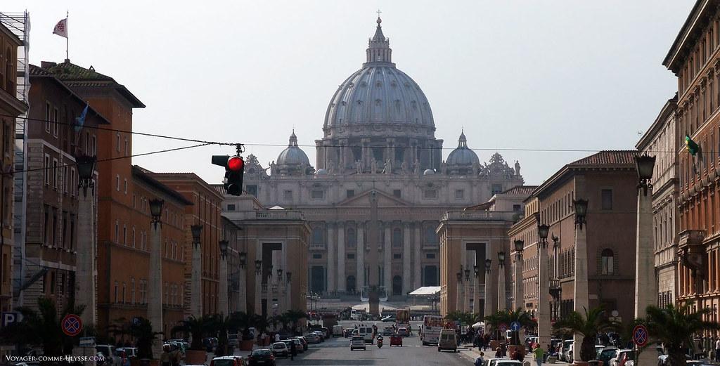 A Via della Conciliazione, no fim da rua, a basílica de São Pedro de Roma. Vemos de cada lado da avenida, a iluminação pública em forma de obelisco. É preciso estar no outro lado da avenida para se poder apreciar a magnifica cúpula da basílica.