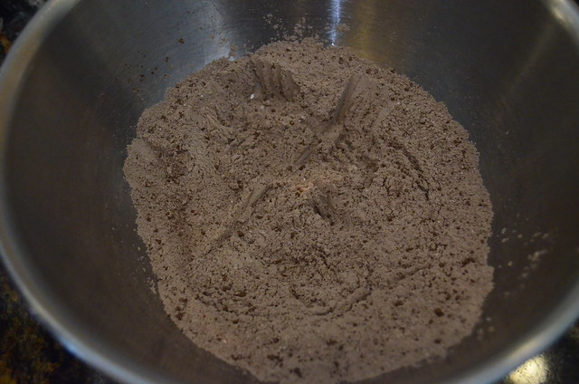A mixture of flour, baking powder, sugar, and cocoa powder in a mixing bowl.