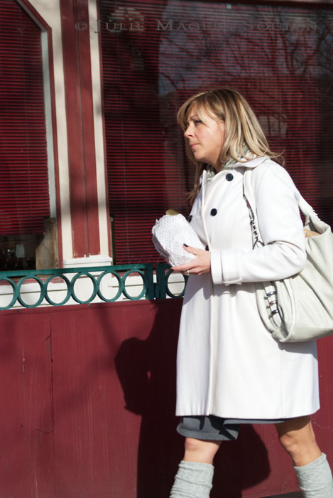 A woman in a white coat next to a red wall grabs a cookie for a quick snack on her way to an unknown destination.
