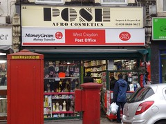 "A small shopfront with a fully glazed front. A selection of wigs is visible in the left-hand window. To the right is an opening in the window with two people facing each other on either side of it, one in the shop and one in the street. A large red telephone box and a red postbox stand on the pavement outside. Above the shop are two signs; the upper one is in black text on a pale brown background and reads ""Posh Afro Cosmetics / Import & Export Ltd / 020 8680 9657"" while the lower one is in red and white and reads ""MoneyGram Money Transfer / West Croydon Post Office / Post Office""."