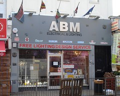 "A mid-terrace ground-floor shop with a large grey sign above a glazed frontage.  The sign reads ""ABM Electrical & Lighting"" with a row of logos underneath including Xpelair, Aurora, and Philips.  The words ""Free Lighting Design Service"" run along the top of the shop window."