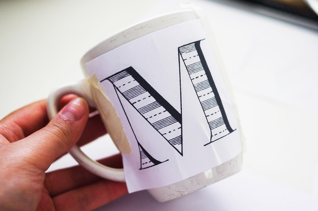 heres a trick i learnt way back when i was in primary school to trace the letter shade the back of the printout with lead pencil tape it to the mugs