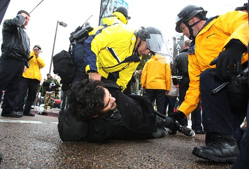 Cops hold down a peaceful activist in San Diego, California during a west coast demonstration aimed at shutting the ports. The events were a continuation of anti-capitalist Occupy manifestations. by Pan-African News Wire File Photos